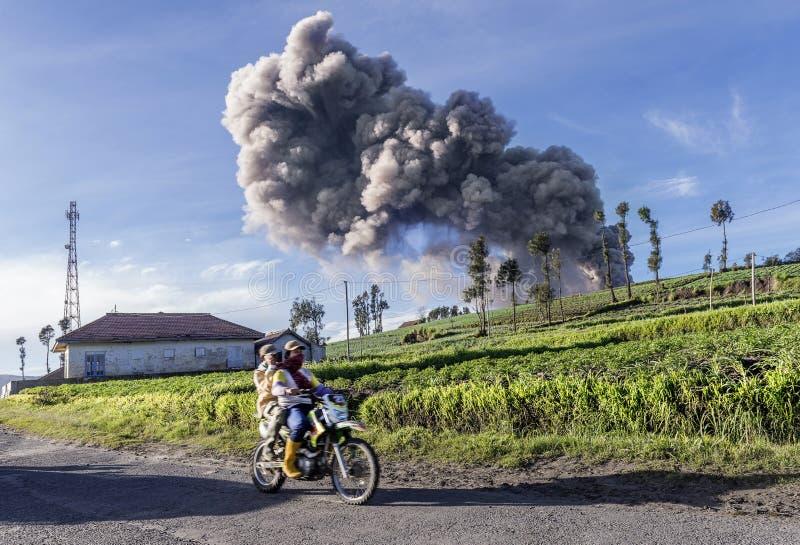 Det lokala byfolket som förbigår lantbrukland som askaen från vulkan, går högt i himlen, då Mt Bromo fick utbrott under Januar royaltyfri fotografi