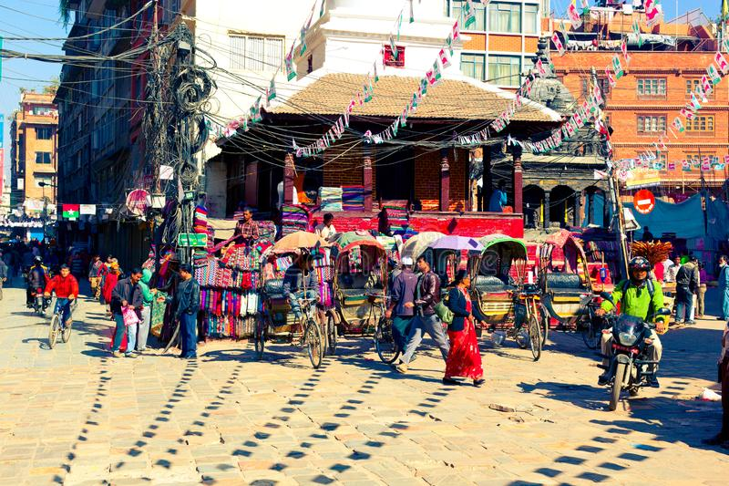 Det lokala folket är upptaget med dagliga angelägenheter på liten stadsfyrkant i Katmandu fotografering för bildbyråer