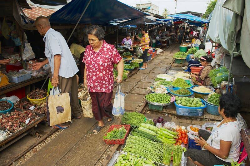 Det lokala folket gör shopping på Mae Klong som järnvägsspår marknadsför i Samut Songkram, Thailand arkivfoton