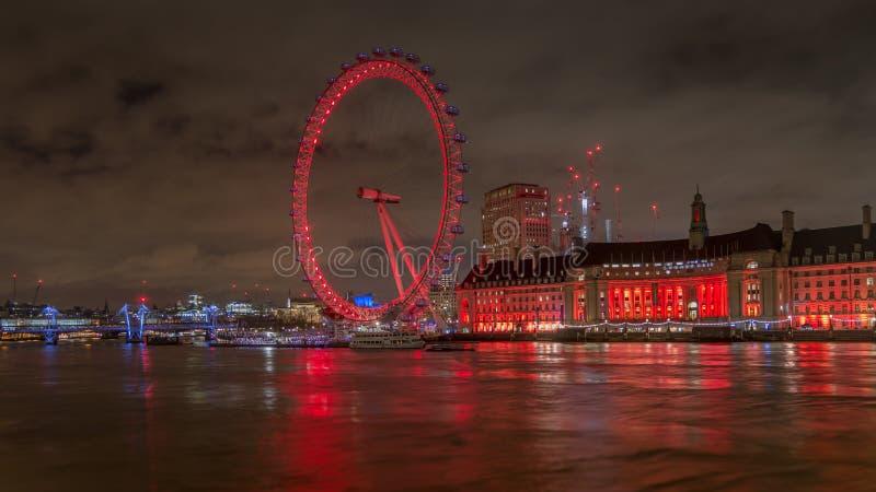 Det London ögat tände med färgrika ljus på natten från den Westminster bron över flodThemsen arkivfoton