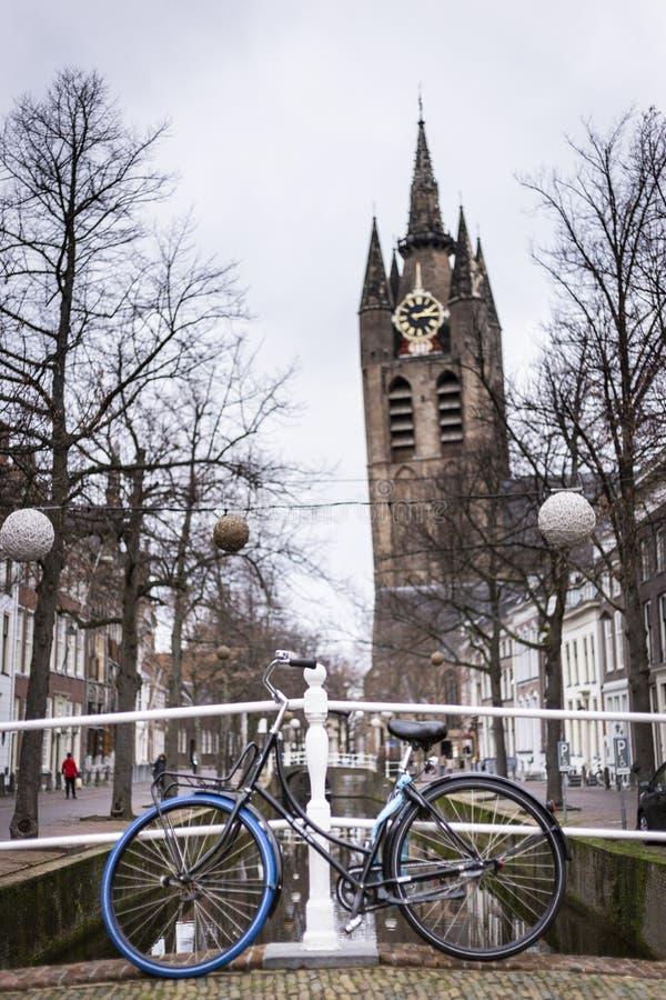 Det lutande tornet av den gamla kyrkan i delftfajans Framme en cykel som lutar mot räcket av arkivfoton