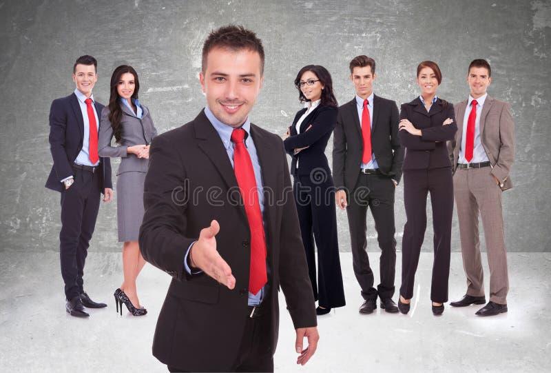 Ung affärsman som välkomnar till laget royaltyfri foto