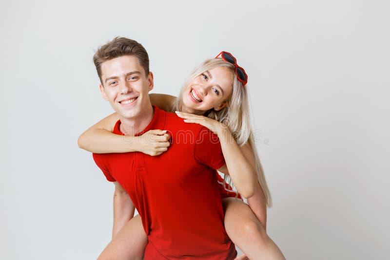 Det lyckliga älskvärda gladlynta unga paret i röd tillfällig blick är krama och le se kameran på vit bakgrund royaltyfria bilder