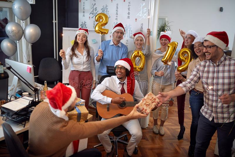 Det lyckliga affärslaget har gyckel och dans i jultomtenhatt på Xmas-parti- och utbytesgåvor arkivfoton
