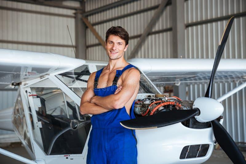Det lyckliga anseendet för flygplanmekaniker med armar korsade nära det lilla flygplanet arkivfoton
