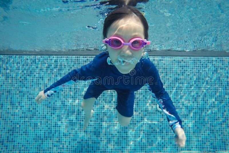 Det lyckliga asiatiska den undervattens- flickabadet och dyken, sommarfamiljsemester med barnet, kopplar av, rolig aktivitet royaltyfri foto