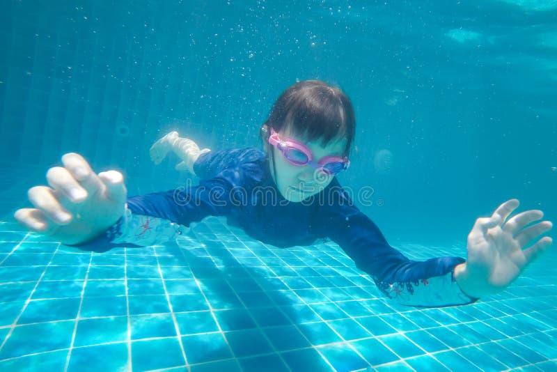Det lyckliga asiatiska den undervattens- flickabadet och dyken, sommarfamiljsemester med barnet, kopplar av, rolig aktivitet arkivbilder