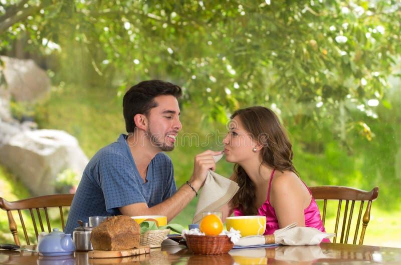 Det lyckliga attraktiva paret äter frukosten tillsammans arkivfoto