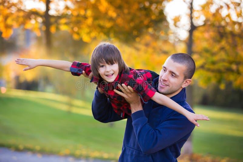Det lyckliga barnet avlar och barnet som har roligt utomhus- i parkera fotografering för bildbyråer