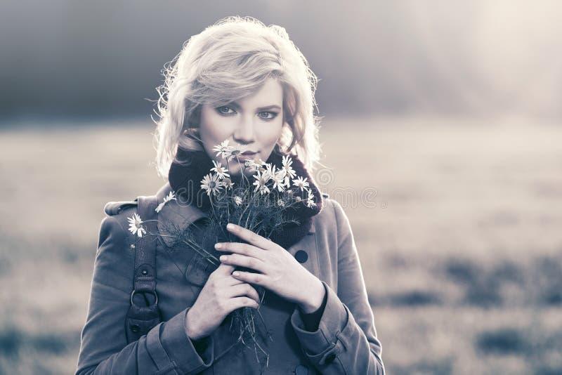 Det lyckliga barnet danar kvinnan med gå för blommor som är utomhus- royaltyfria bilder
