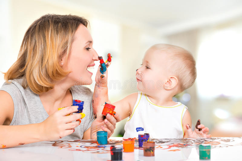 Det lyckliga barnet drar på framsidan av hans moder. arkivfoton