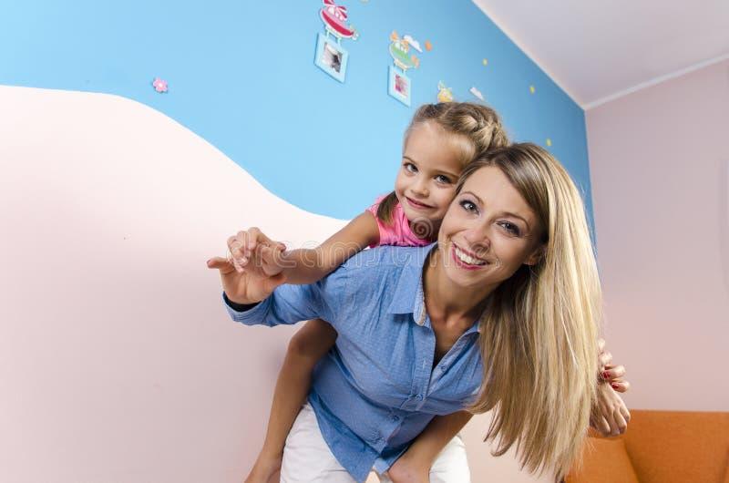 Det lyckliga barnet fostrar att bära hennes förtjusande liten flicka på henne tillbaka arkivfoton