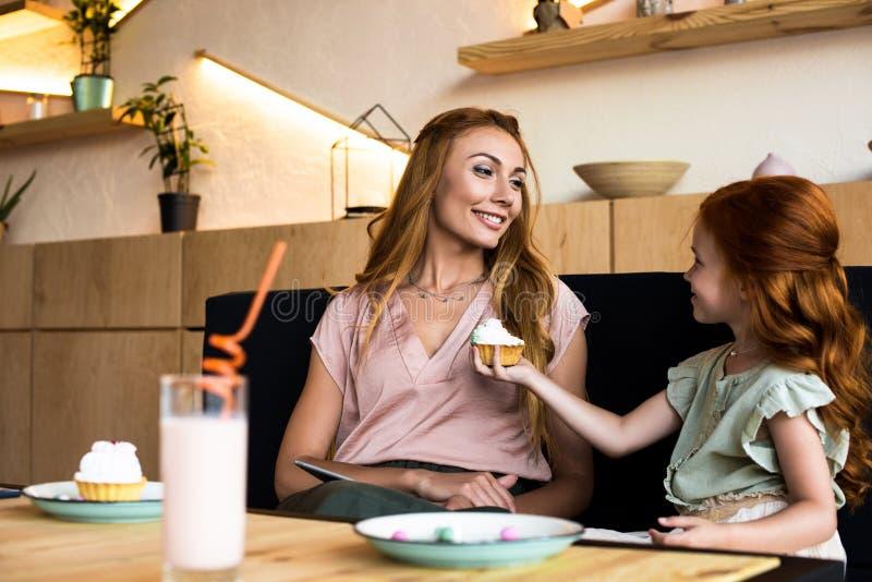 det lyckliga barnet fostrar att se den hållande muffin för den lilla rödhårig mandottern arkivfoto