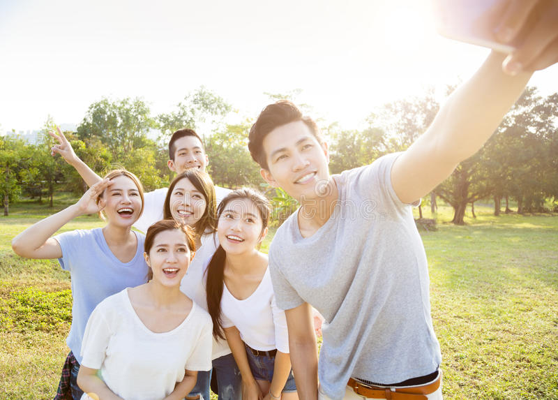 Det lyckliga barnet grupperar att ta selfie i parkera arkivfoton