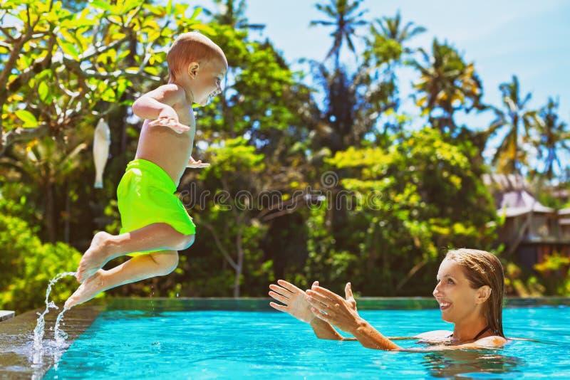 Det lyckliga barnet hoppar till moderhänder i simbassäng royaltyfri fotografi