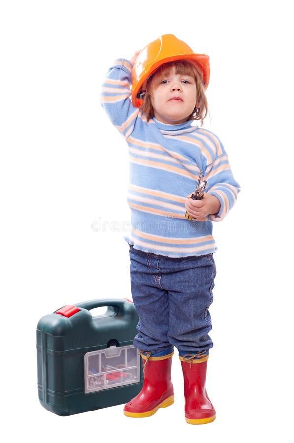 Det lyckliga barnet i hardhat med bearbetar arkivbild