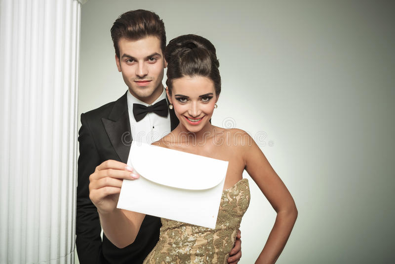 Det lyckliga barnet kopplar ihop att framlägga en invitera till deras bröllop arkivbilder