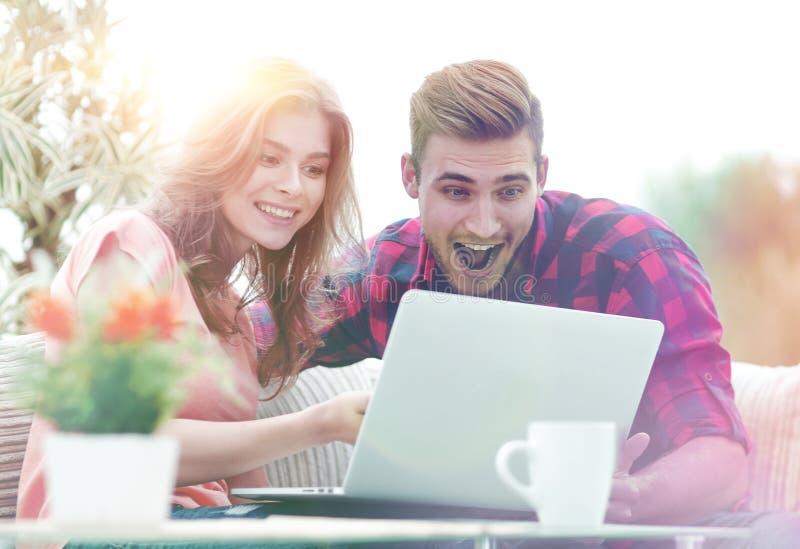 Det lyckliga barnet kopplar ihop att hålla ögonen på en favorit- film, medan sitta i en modern vardagsrum fotografering för bildbyråer