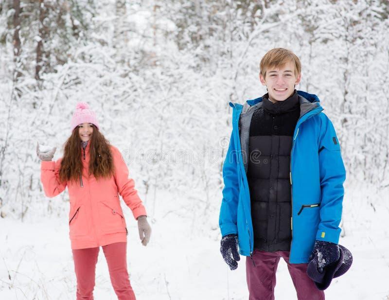 Det lyckliga barnet kopplar ihop att ha gyckel tillsammans i insnöad vinterskog fotografering för bildbyråer
