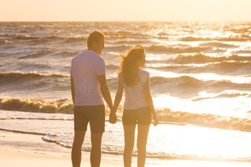 Det lyckliga barnet kopplar ihop att koppla av på stranden på solnedgången Familjresande fotografering för bildbyråer