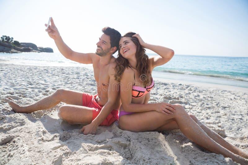 Det lyckliga barnet kopplar ihop att ta selfie, medan sitta på stranden arkivfoton
