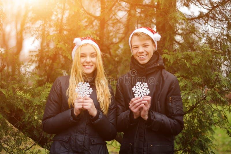 Det lyckliga barnet kopplar ihop förälskade bärande jultomtenhattar och arkivbild