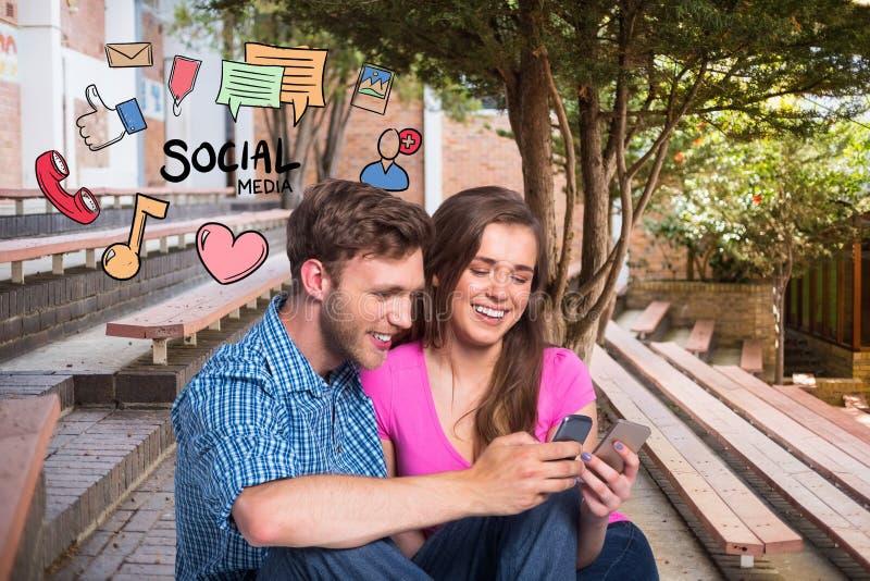 Det lyckliga barnet kopplar ihop genom att använda socialt massmedia på mobiltelefoner vid symboler arkivbilder