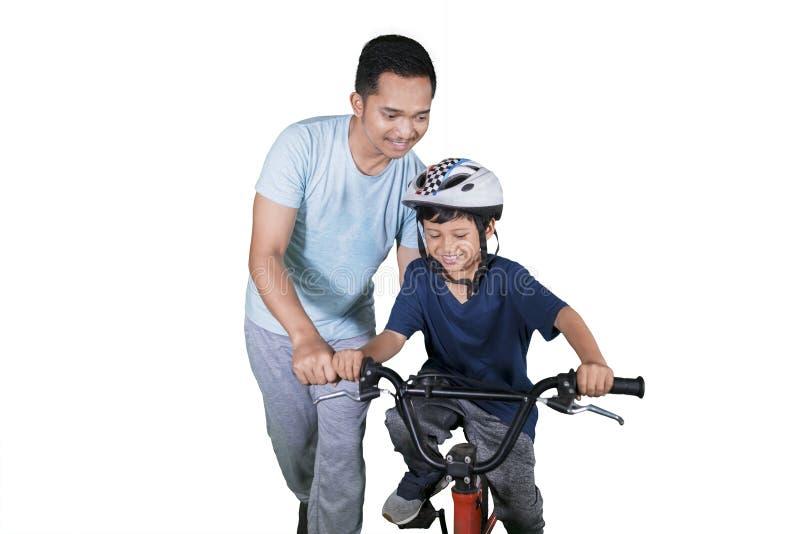 Det lyckliga barnet lär att rida en cykel med hans fader royaltyfri fotografi