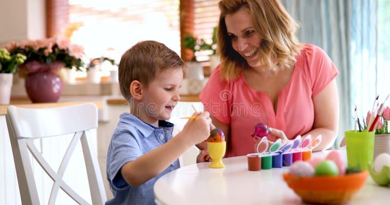 Det lyckliga barnet moder och son målar påskägg royaltyfri fotografi