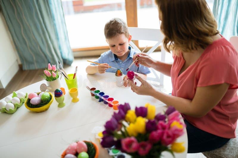 Det lyckliga barnet moder och son målar påskägg royaltyfri bild