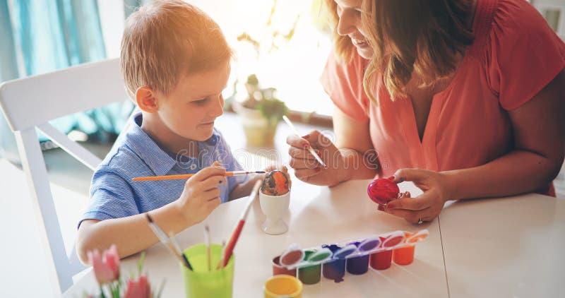 Det lyckliga barnet moder och son målar påskägg arkivbild