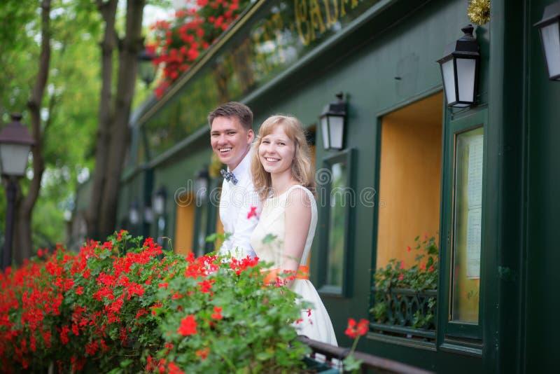 Det lyckliga barnet nyligen-gifta sig par på en balkong royaltyfri bild