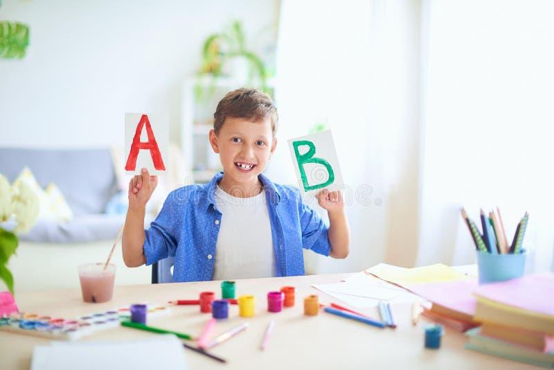 Det lyckliga barnet på tabellen med skolatillförsel ler roligt och lär alfabetet i en skämtsam väg positiv student i ett ljust royaltyfria bilder