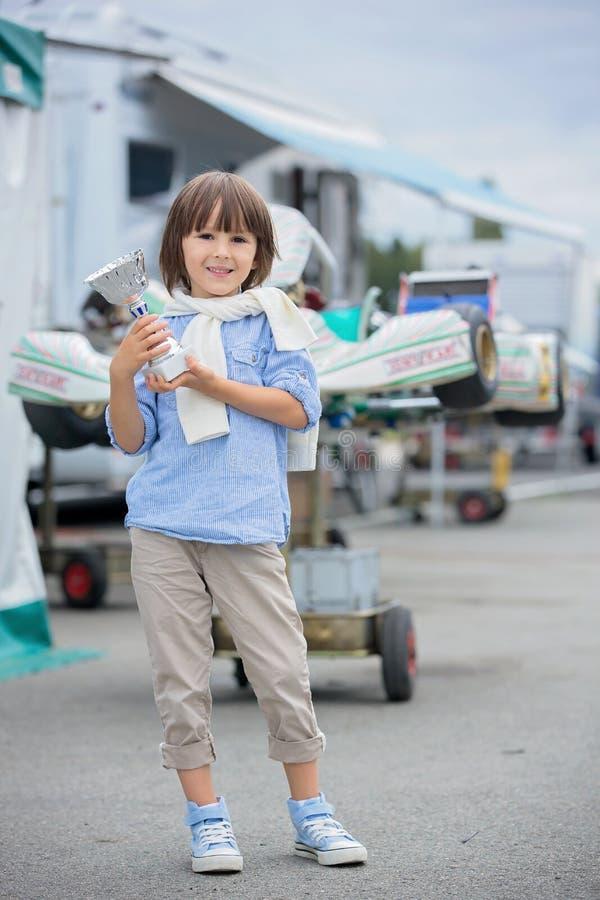Det lyckliga barnet, pojken, den hållande mästerskapkoppen, vinnare på går vagnsrommar arkivfoton