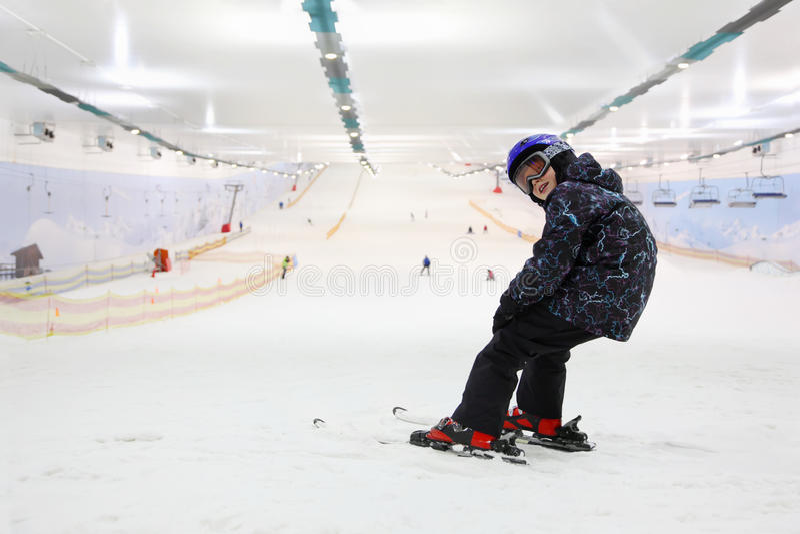 det lyckliga barnet skidar standing arkivfoton