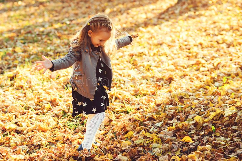 Det lyckliga barnet som går i höst, parkerar Behandla som ett barn flickan som kastar upp de stupade sidorna Härlig guld- hösttid royaltyfri bild