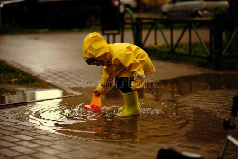 Det lyckliga barnet spelar i en pöl på en regnig dag för sommar en pojke i en gul regnrock går i parkerar royaltyfria foton