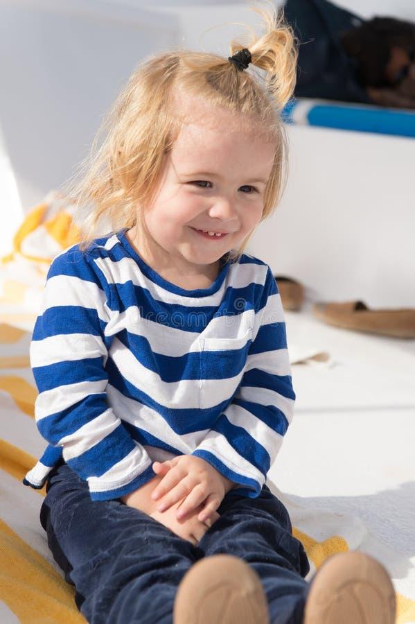 Det lyckliga barnet tycker om solig dag Pysleende i marinkläder Unge som ler med hästsvansen för blont hår Ungar danar och utform arkivbild