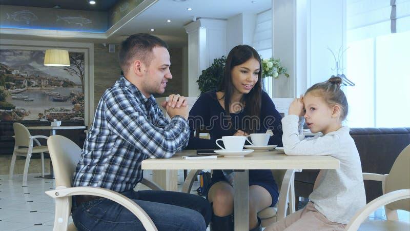 Det lyckliga barnet uppfostrar att prata witndottern under deras familjsemester i kafé som dricker te fotografering för bildbyråer