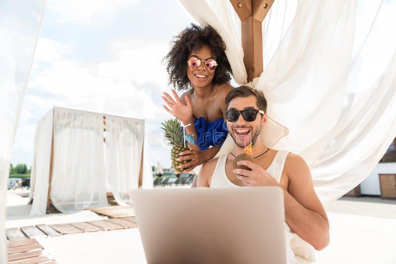 Det lyckliga barnet uppsökte man- och mulattkvinnan som talar via internet royaltyfri fotografi