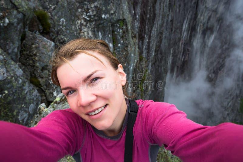 Det lyckliga folket kopplar av i klippa under turen Norge fotvandra route royaltyfri bild