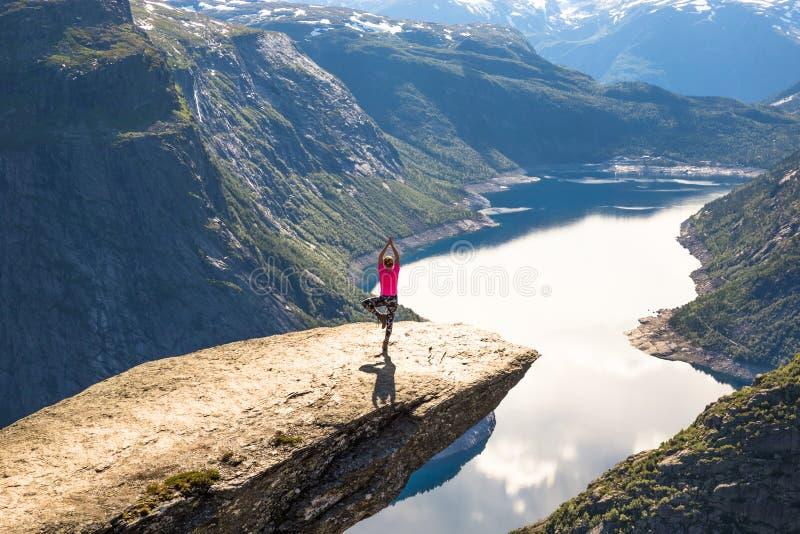 Det lyckliga folket kopplar av i klippa under turen Norge Trolltunga som fotvandrar rutten royaltyfria bilder