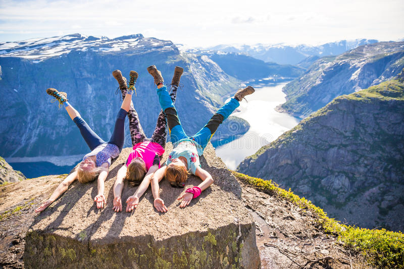 Det lyckliga folket kopplar av i klippa under turen Norge Trolltunga som fotvandrar rutten royaltyfri bild