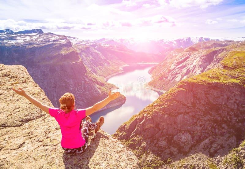 Det lyckliga folket kopplar av i klippa under turen Norge Trolltunga som fotvandrar rutten Tona bilden fotografering för bildbyråer