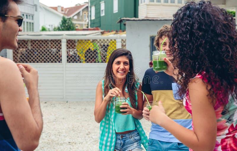Det lyckliga folket med drycker som skrattar i sommar, festar royaltyfria bilder
