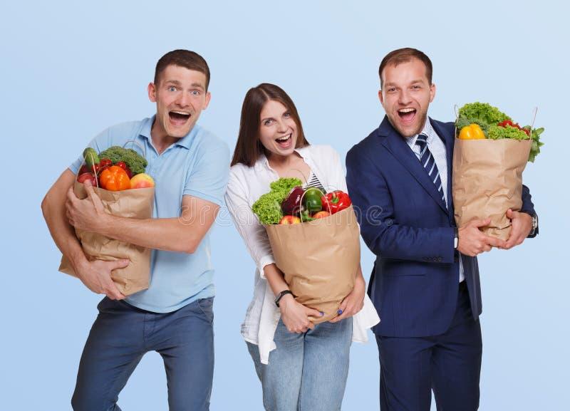 Det lyckliga folket rymmer påsar med sund mat, isolerade livsmedelsbutikköpare royaltyfri foto