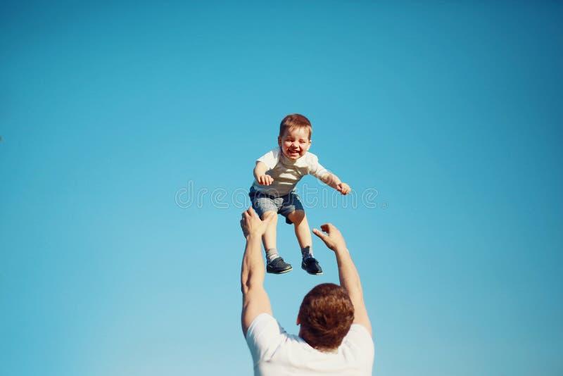Det lyckliga glade barnet, fadergyckel kastar upp sonen i luften, sommar royaltyfria bilder