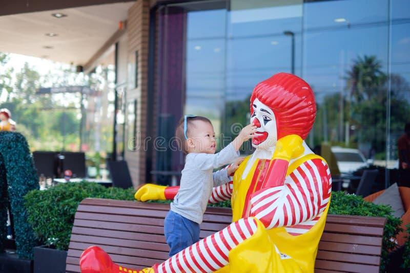 Det lyckliga gulliga lilla asiatiska lilla barnet behandla som ett barn pojkebarnlek med Ronald McDonald royaltyfri foto