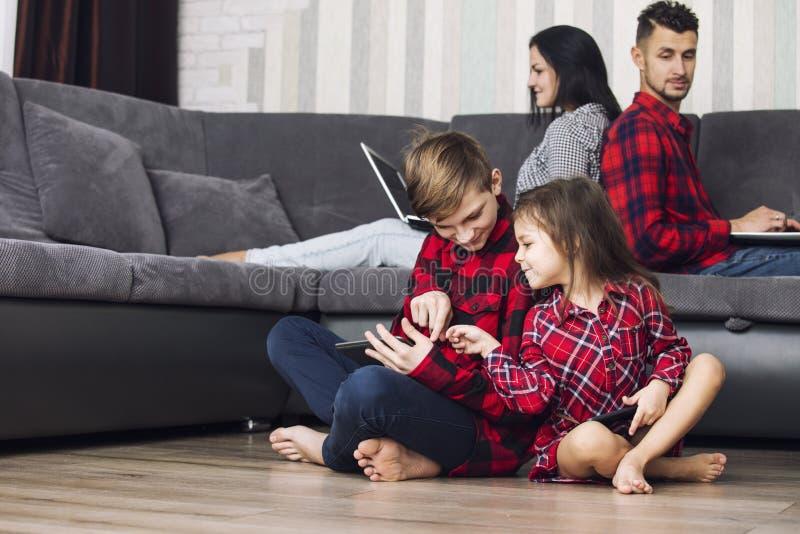 Det lyckliga härliga familjhemmet med bärbara datorer och minnestavlor sitter i arkivfoton