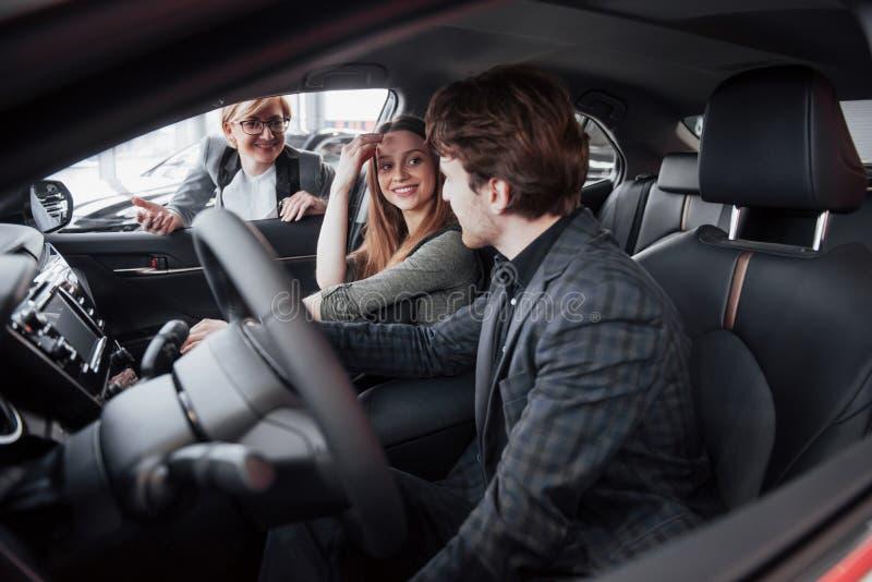 Det lyckliga härliga paret väljer en ny bil på återförsäljaren royaltyfri fotografi